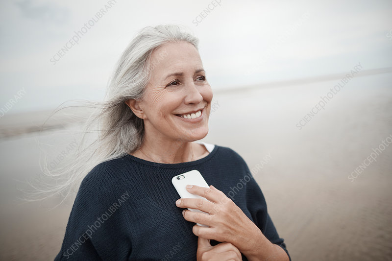 Senior woman holding cell phone on beach
