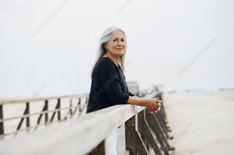 Portrait senior woman leaning on beach railing