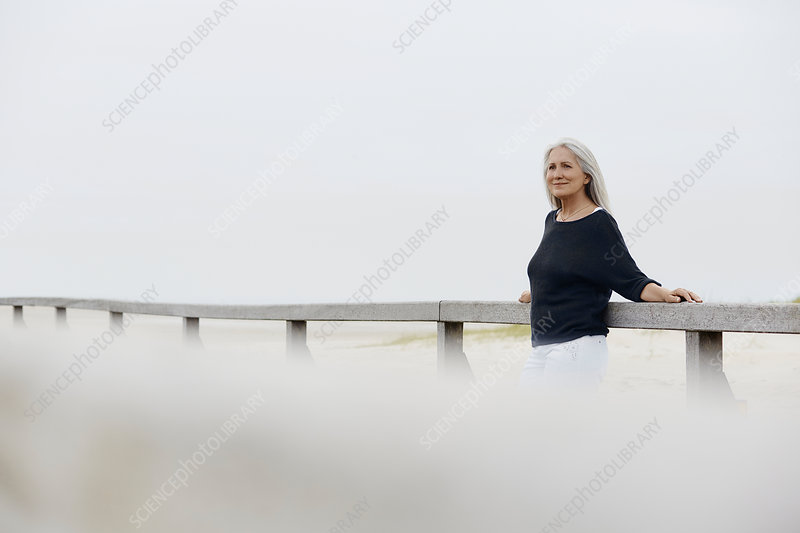 Confident senior woman leaning on beach railing