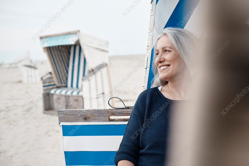 Smiling senior woman looking away on beach