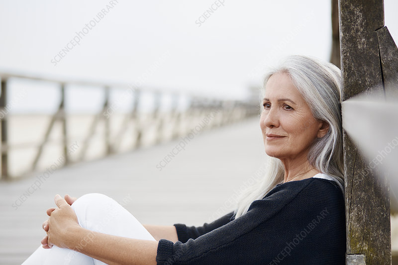 Pensive senior woman relaxing on beach boardwalk