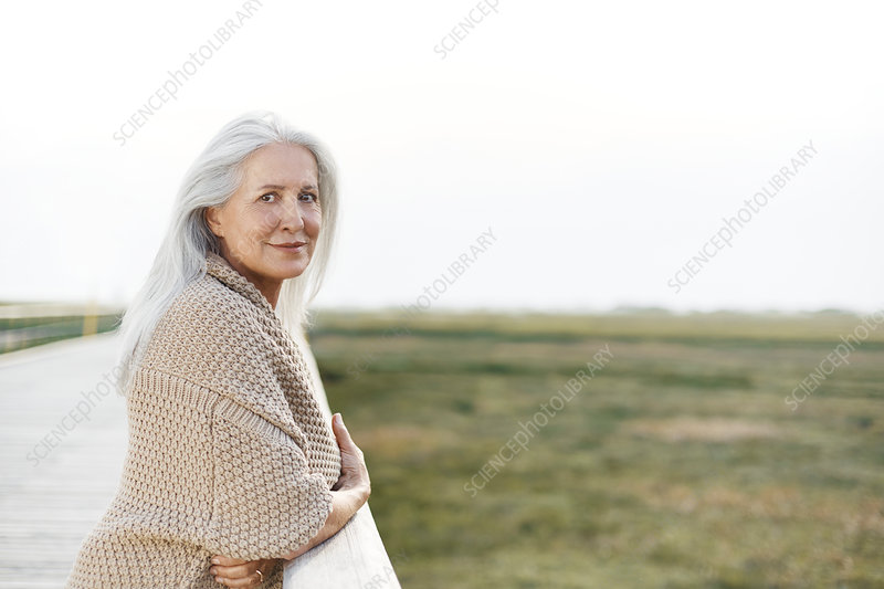 Portrait senior woman leaning on boardwalk railing