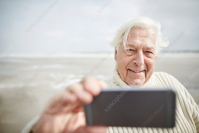 Senior man taking selfie with cell phone on beach