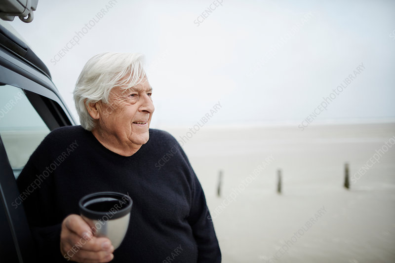 Happy senior man drinking coffee at car on beach