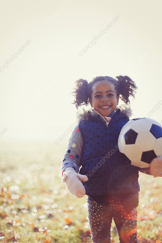 Portrait girl with soccer ball in autumn park