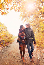 Affectionate couple walking on path in autumn park