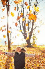 Playful girl throwing leaves overhead