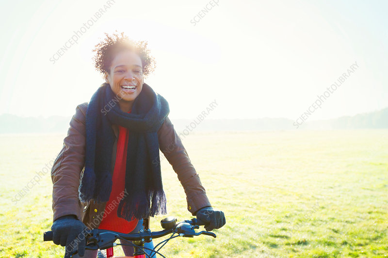Smiling woman bike riding in park grass