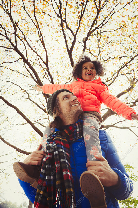 Father carrying enthusiastic daughter on shoulders