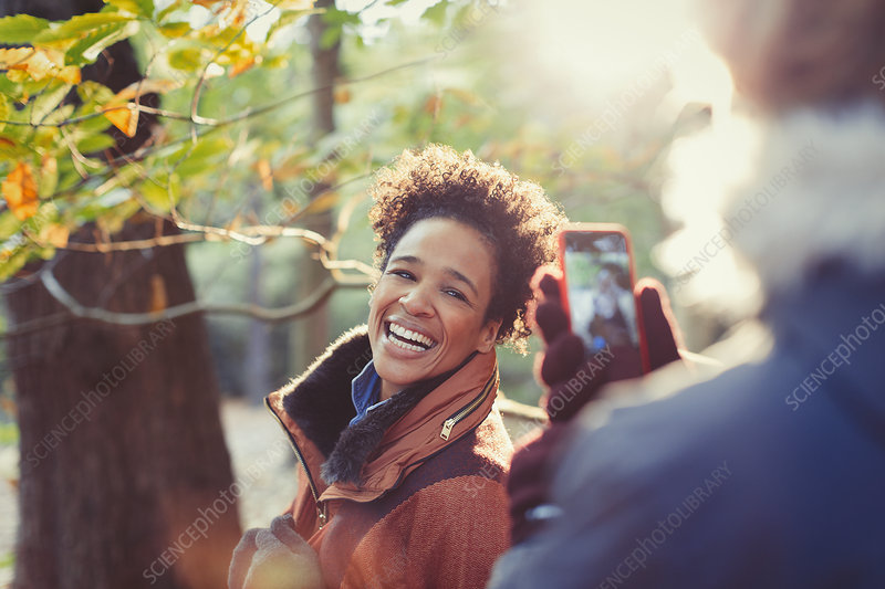 Smiling woman posing for boyfriend in autumn woods