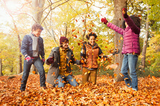 Playful young family throwing leaves in woods