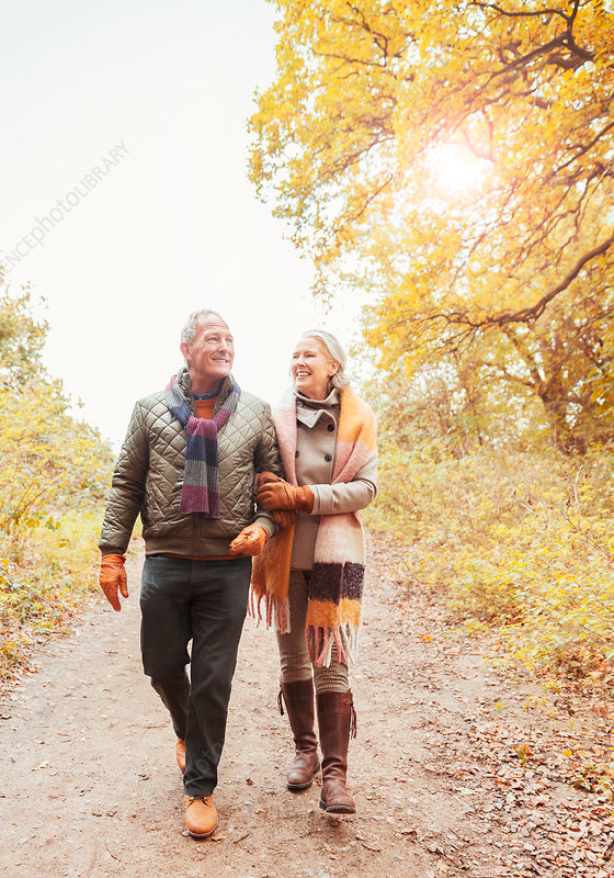 Senior couple walking arm in arm on path in woods
