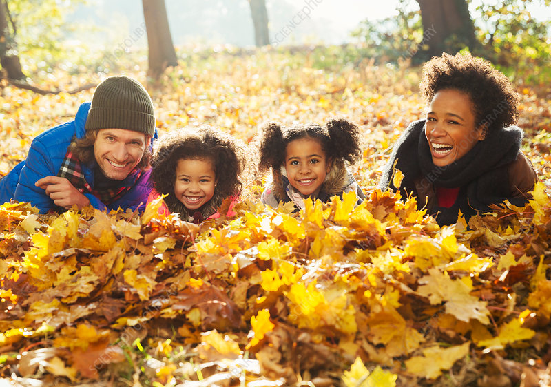 Portrait young family laying in autumn leaves