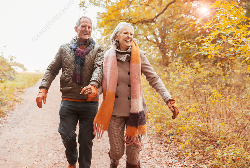 Senior couple holding hands walking on path