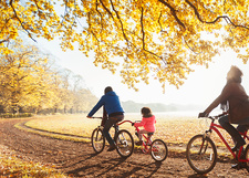 Young family bike riding on path in autumn woods