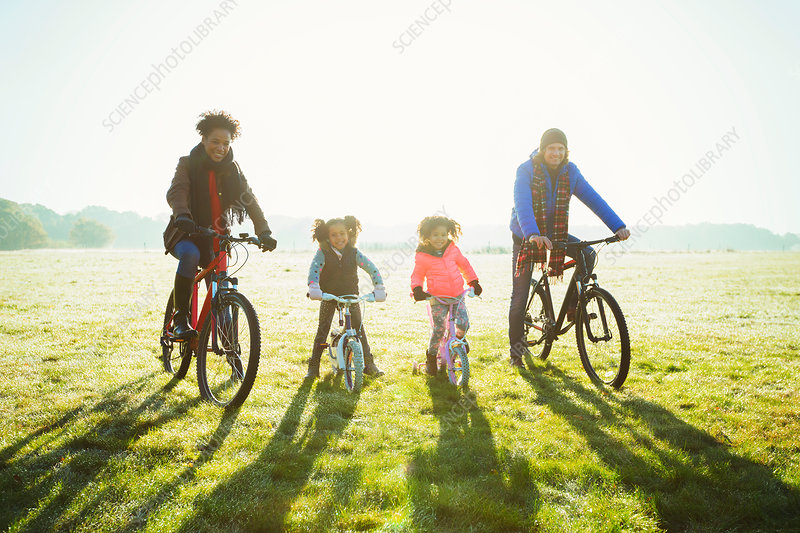 Portrait young family bike riding grass