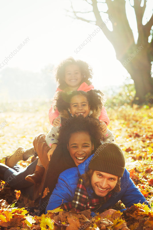 Family laying on top of each other in leaves