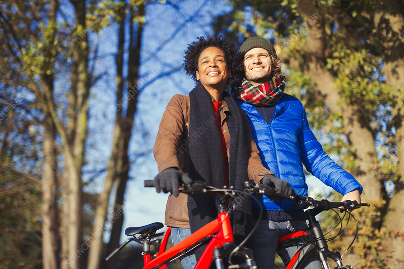 Smiling couple with bicycles in autumn park