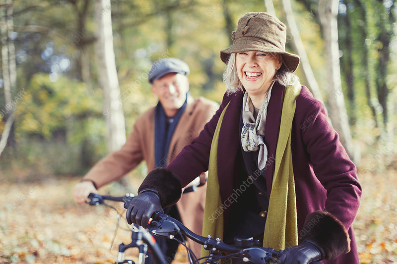 Smiling senior couple bike riding in autumn woods