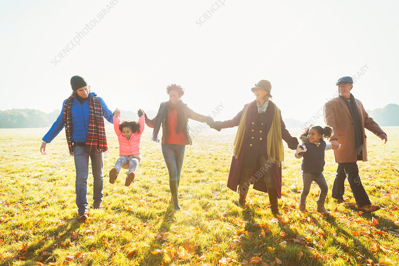 Playful family walking in autumn park grass