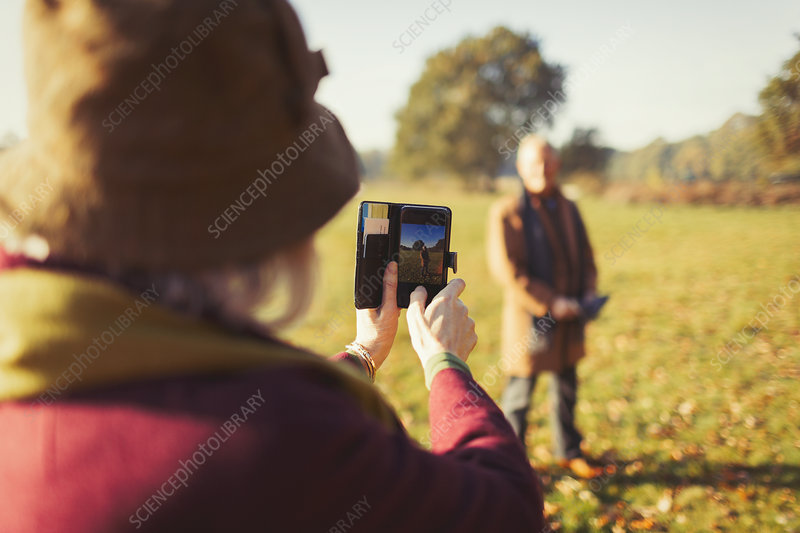 Senior woman photographing husband in autumn park