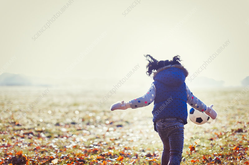 Girl playing soccer in autumn park grass