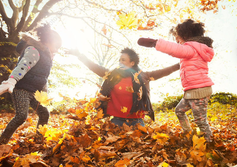 Playful mother and daughters throwing leaves