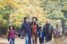 Multi-generation family walking in autumn woods
