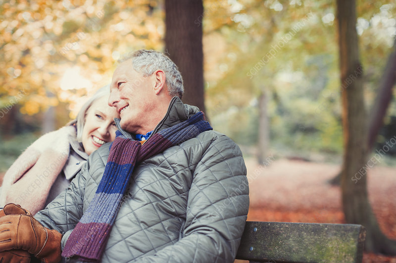 Affectionate senior couple on bench in autumn park