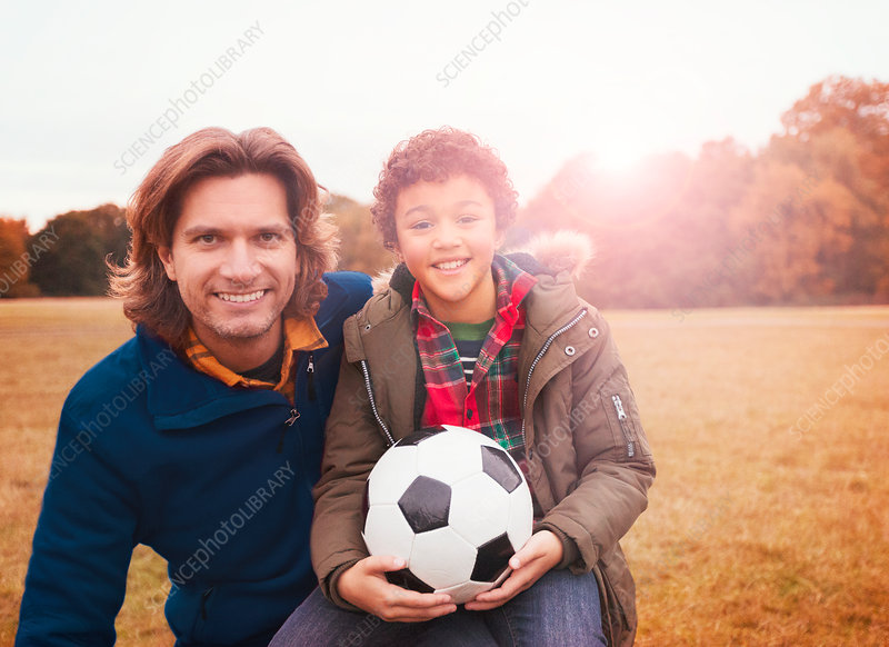 Portrait father and son with soccer ball grass