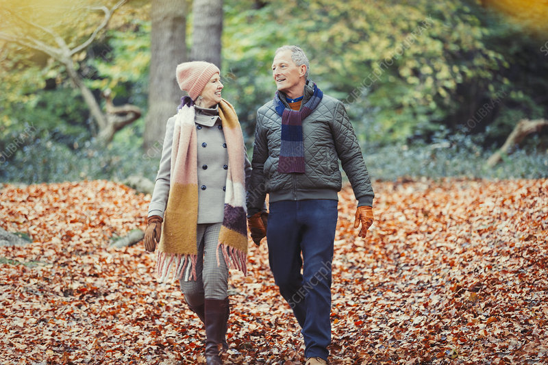 Senior couple walking in autumn leaves in park