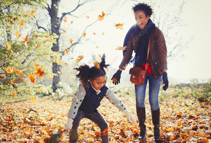 Playful mother and daughter throwing leaves