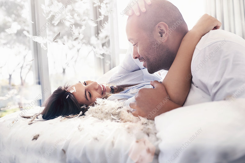 Pillow feathers falling around couple on bed