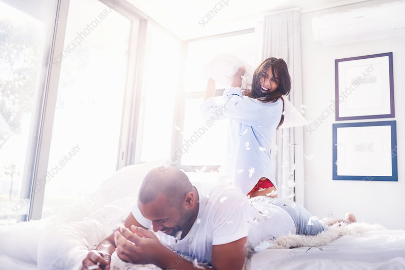 Playful couple pillow fighting in bedroom