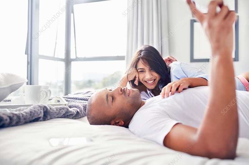 Smiling couple laying and relaxing on bed