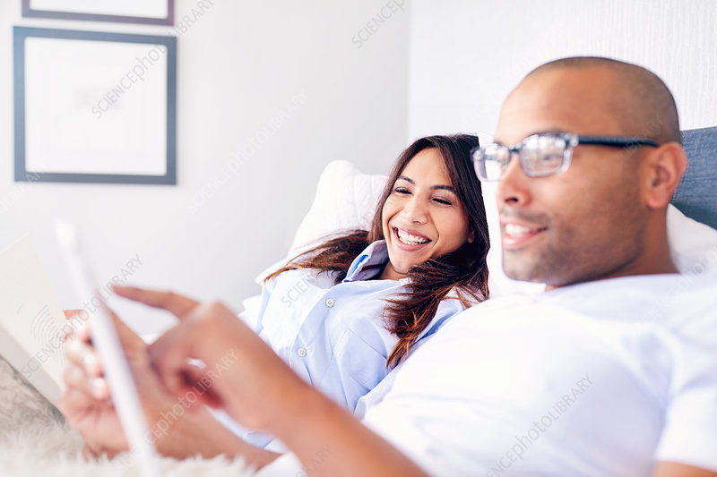 Smiling couple using tablet on bed