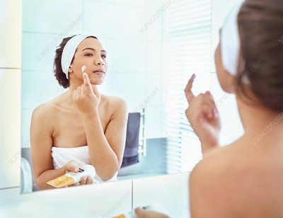 Woman applying moisturizer to cheek