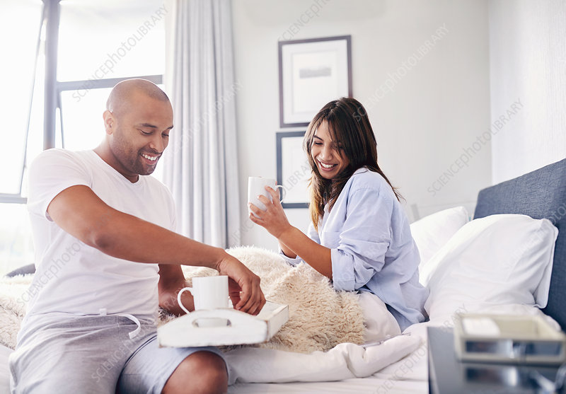 Smiling couple drinking coffee in bed