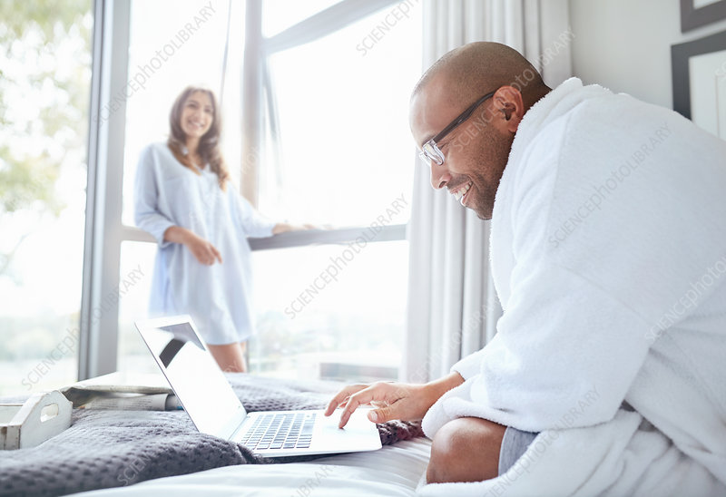 Smiling woman watching boyfriend in bathrobe