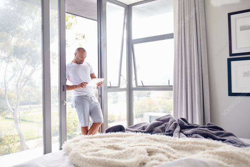 Man using tablet at bedroom window