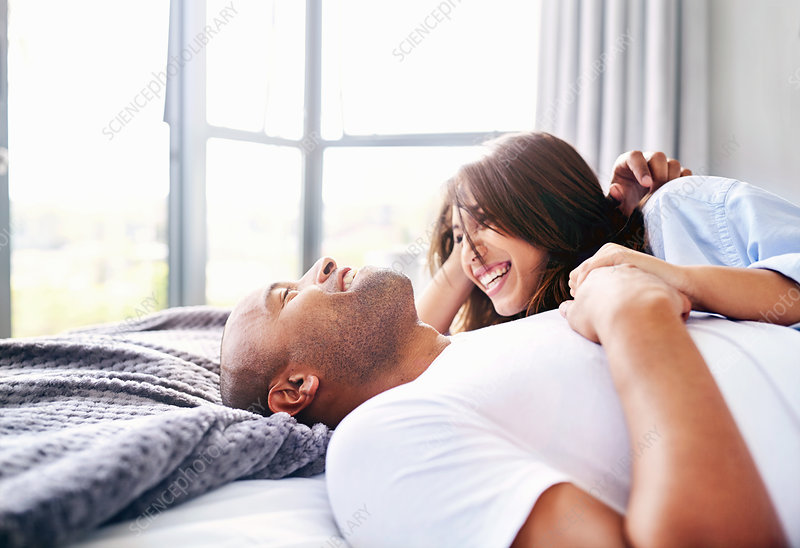 Smiling couple laying and cuddling on bed