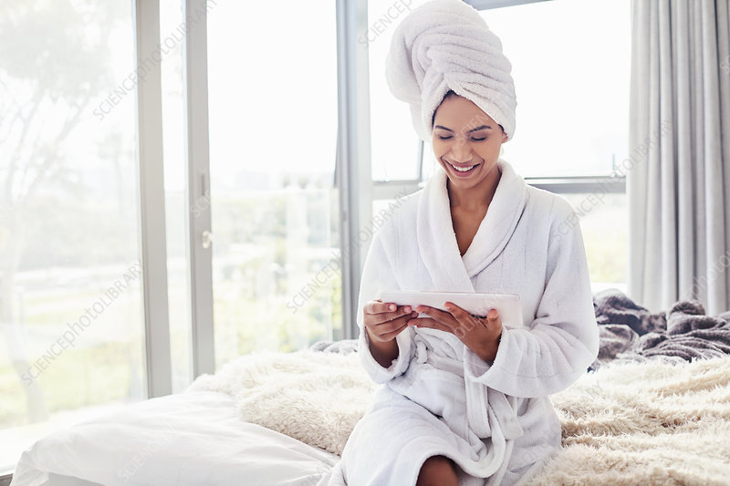 Smiling woman in bathrobe using tablet on bed