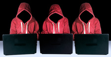 Hooded figures hacking laptop computers