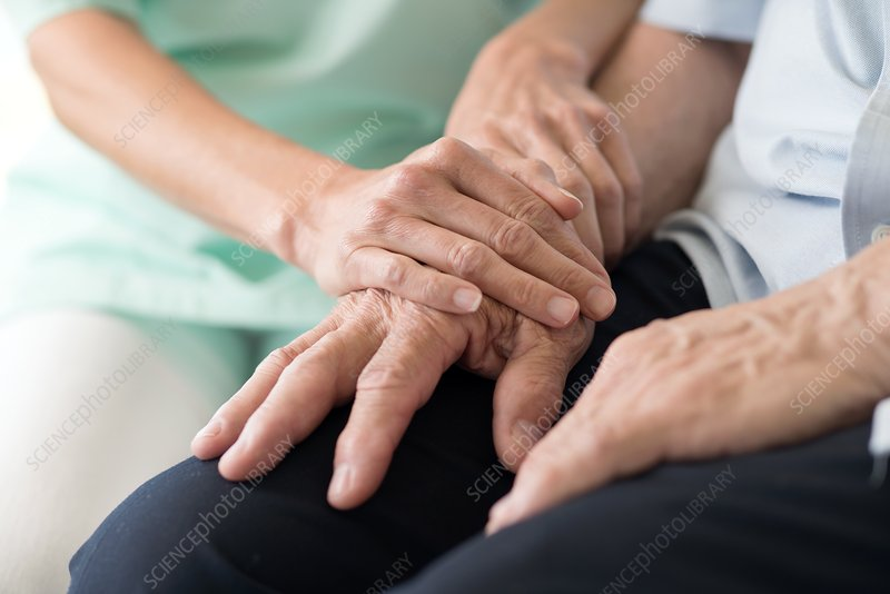 Care worker holding senior man's hands