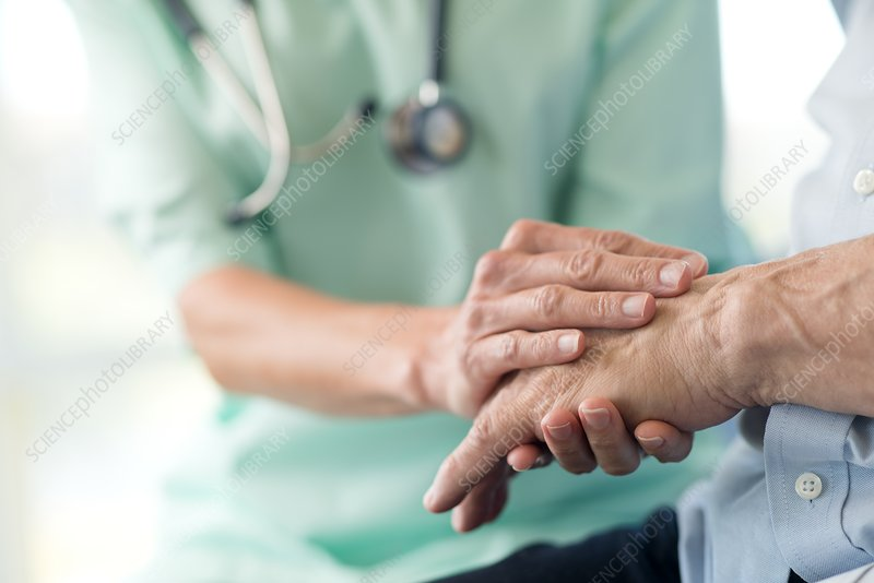 Care worker holding senior man's hand