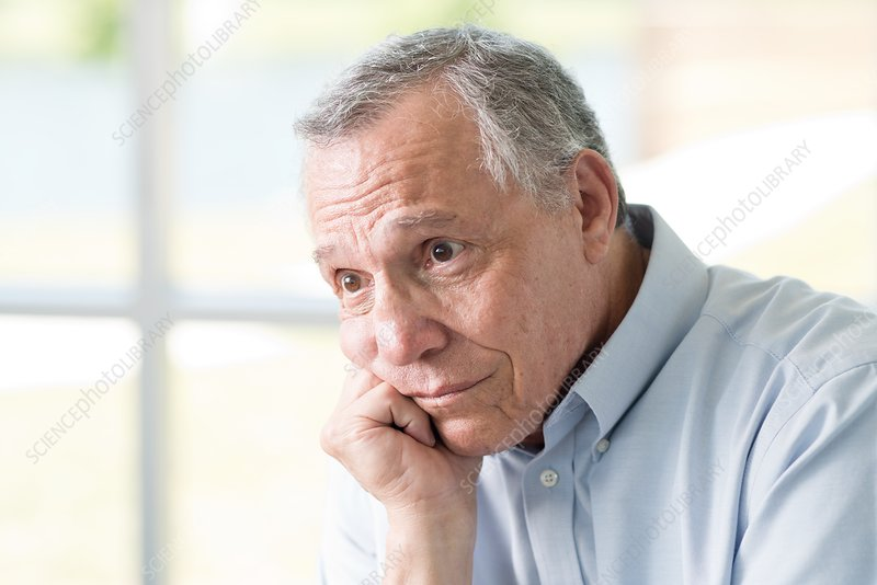 Senior man with hand on chin looking away
