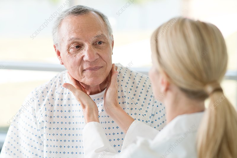 Female doctor touching senior man's neck