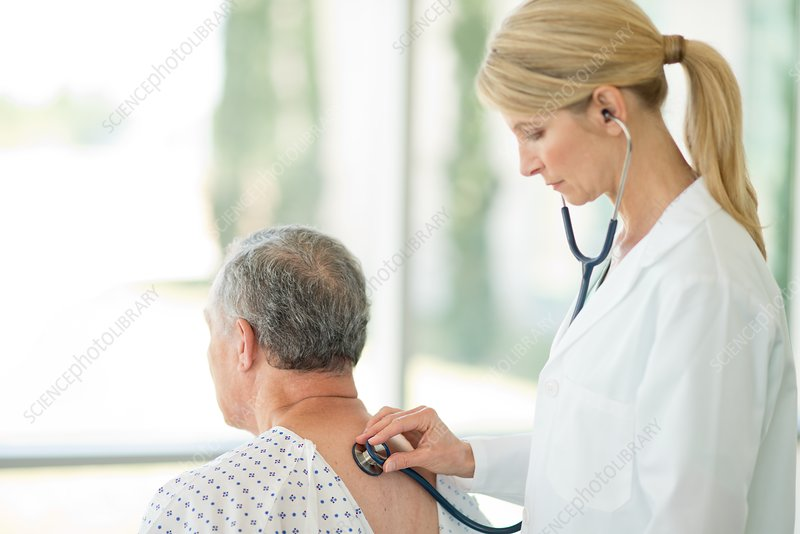 Female doctor using stethoscope on male patient