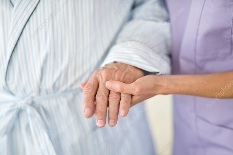 Care worker holding senior patient's hand