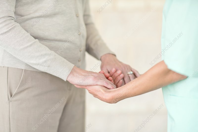 Care worker holding senior woman's hands